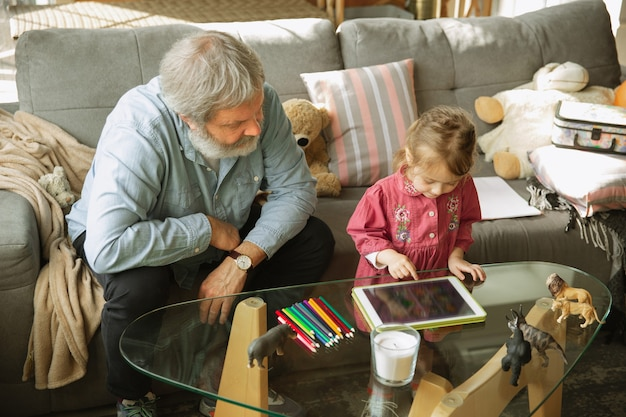 Grandfather and grandchild playing together at home. happiness, family, relathionship, learning and education concept. sincere emotions and childhood. reading books, drawing, playing with puzzles.