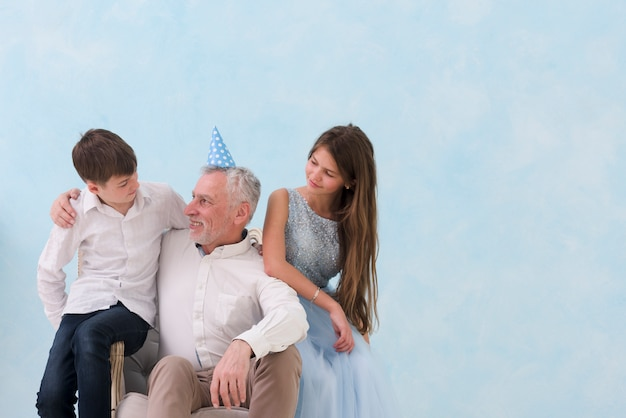 Grandfather and grandchildren sitting on arm chair on blue background