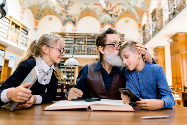 Grandfather and grandchildren sitting at the table in library and reading book