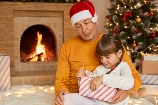 Grandfather and granddaughter open christmas gift