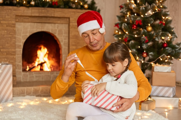 Grandfather and granddaughter opening christmas presents, posing in living room with new year decoration, kid sitting on man's knees, being concentrated, look at box, posing near fireplace.