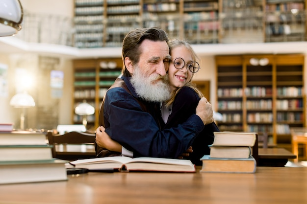 Grandfather and granddaughter or senoir teacher and pupil student, sitting at the table and hugging each other, in old vintage city library. reading, education concept