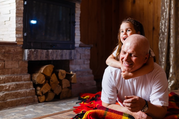 Grandfather and granddaughter sitting at home near the fireplace and hugging