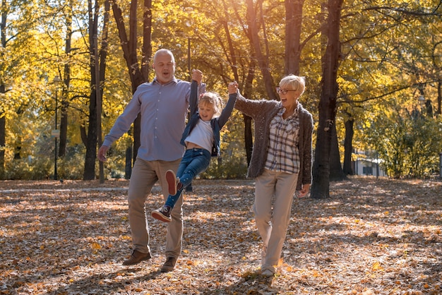 Grandfather and grandmother playing with their grandson in a park