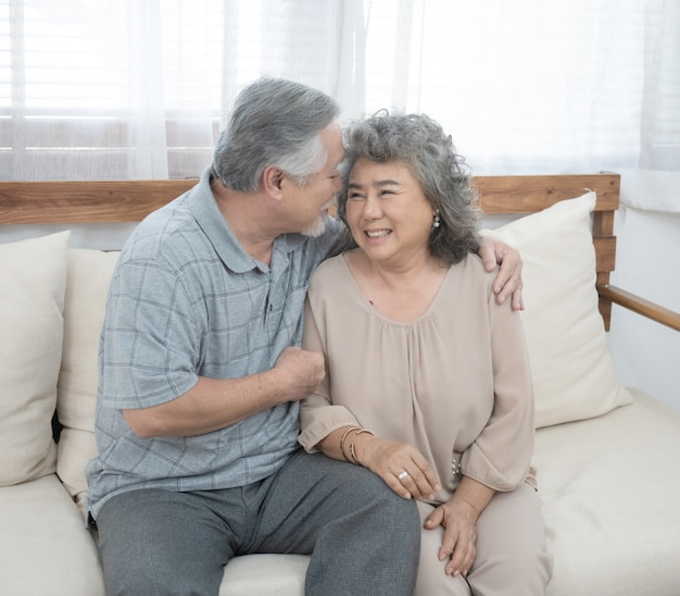 Grandfather and grandmother sit on coach in living room at home have leisure time in retirement lifestyles.