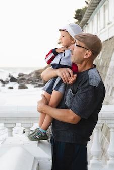 Grandfather and grandson loking away at sea