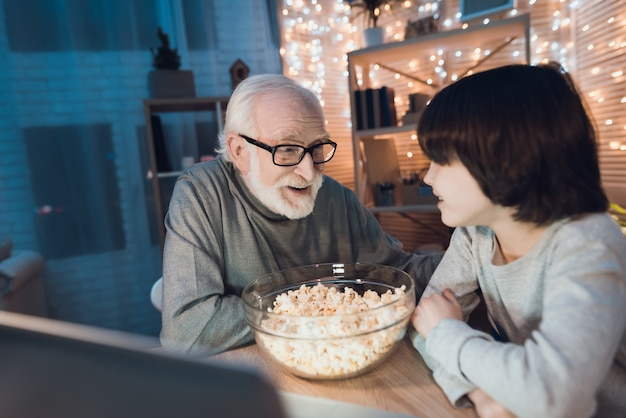 Grandfather and grandson watching movie on laptop