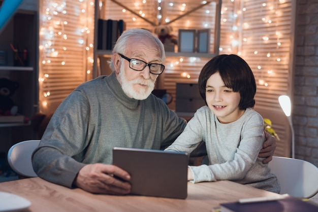 Grandfather and grandson watching movie on tablet