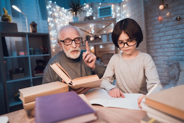 Grandfather helping grandson with doing homework