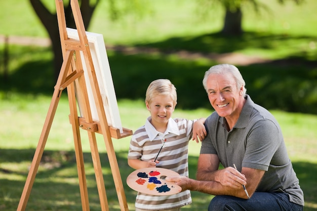 Grandfather and his grandson painting in the garden