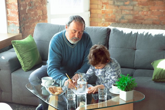 Grandfather and his grandson spending time insulated at home, studying