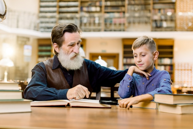 Grandfather his grandson, teacher and student, sitting at the table in ancient library