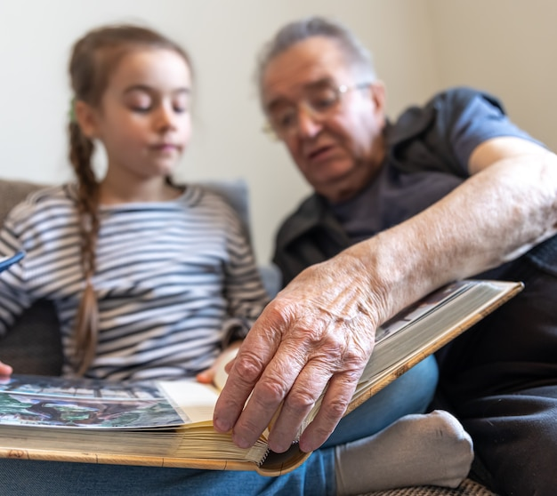 Grandfather and his little granddaughter are looking at pictures in the family photo album.