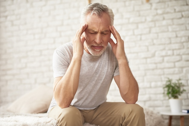 Grandfather holding head blood pressure headache.