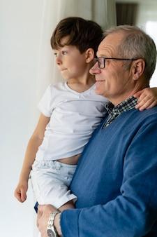 孫を窓際に抱きかかえる祖父