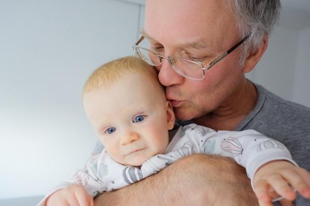 祖父の腕を握って、かわいい青い目をした赤ちゃんにキスします。クローズアップショット。育児や子供の頃のコンセプト