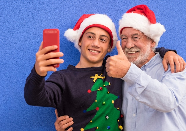 Grandfather hugs his teenage grandson while both wearing a santa hat smiling while taking a selfie