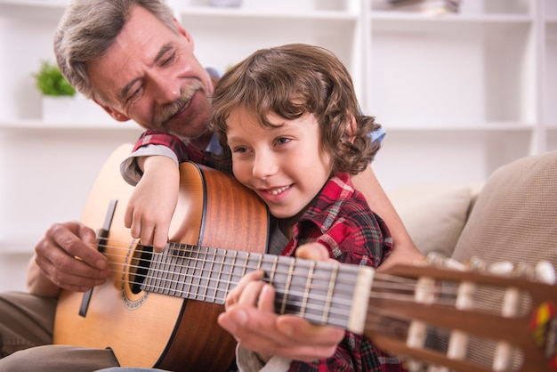 Grandfather is playing guitar with his grandson.