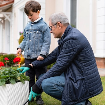 Grandfather and little boy working in the garden