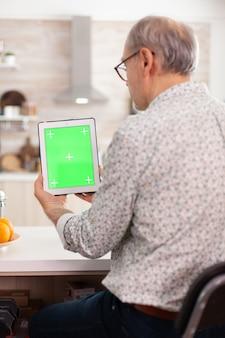현대적인 주방에서 아침 식사를 하는 동안 녹색 화면이 있는 태블릿 pc를 보고 있는 할아버지. 메모장을 들고 쉽게 교체할 수 있도록 크로마 키 격리 모형 모형이 있는 노인