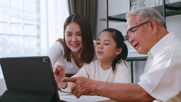 Grandfather and mother are teaching daughter homework while studying online at home.