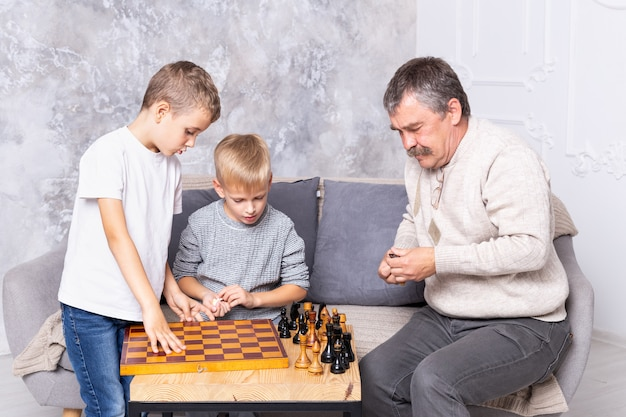 Grandfather playing chess with grandchildren. the boys and grandpa are sitting on the sofa in the living room and playing. senior man teaches a child to play chess