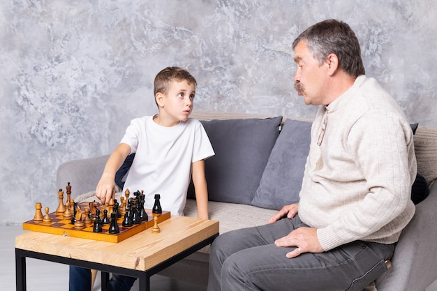 Grandfather playing chess with grandson indoor. the boy and his grandpa are sitting on the sofa in the living room and talking together