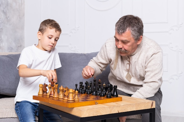 Grandfather playing old chess with grandson indoor. the boy and his grandpa are sitting on the sofa in the living room and playing. senior man teaches a child to play chess