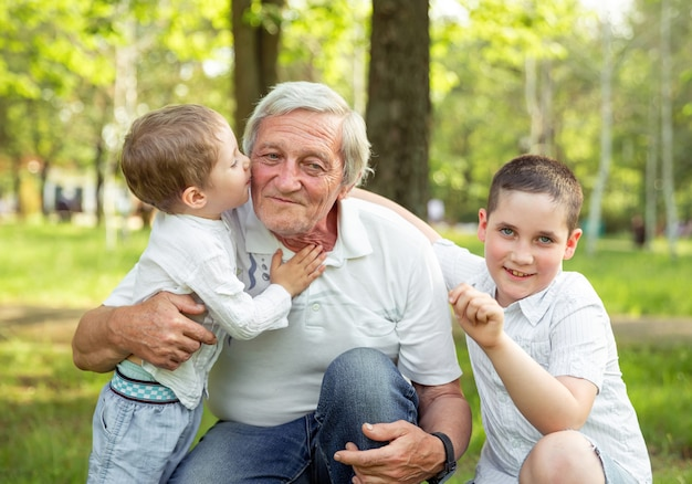 Grandfather playing with grandchildren. boys hugging his grandfather