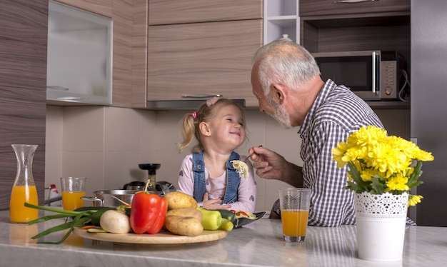 祖父が孫娘と台所で遊んでいる