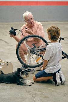 祖父が犬の近くで孫と自転車の車輪をポンプでくみます