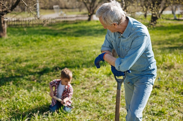 Grandfather resting on a wooden shovel hand and looking at his little grandchild helping him in a garden and scooping the earth