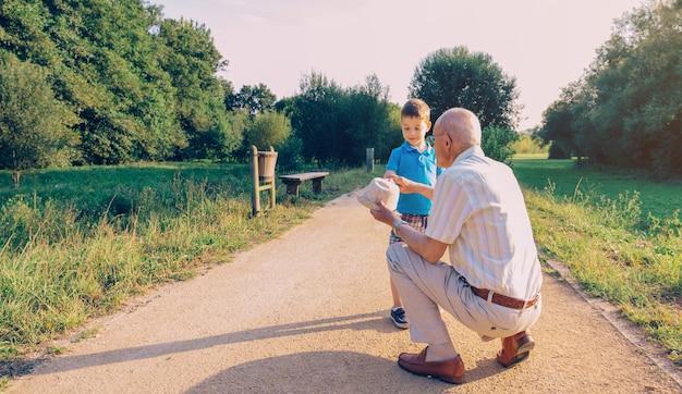 자연 경로 배경 위에 손자에게 그의 모자를 보여주는 할아버지. 두 개의 다른 세대 개념입니다.