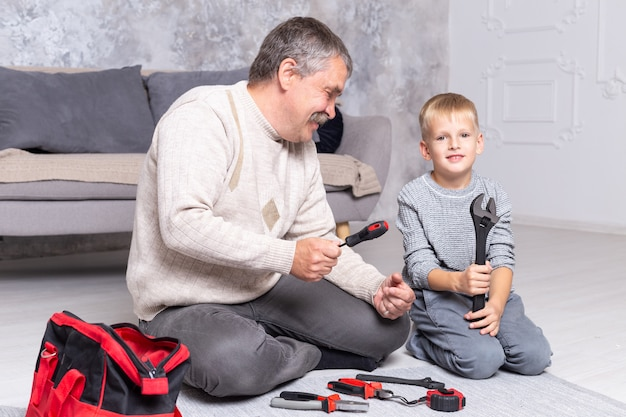 Grandfather shows his grandson repair tools while sitting on the floor near the sofa