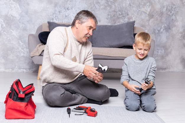 Grandfather shows his grandson repair tools while sitting on the floor. senior man teaches a boy to repair