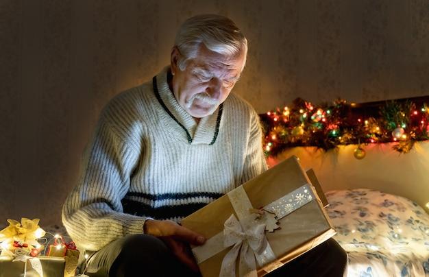 花輪の光のある部屋でクリスマスプレゼントを開くソファに座っている祖父