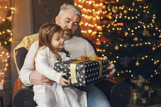 Grandfather sitting with his granddaughter. celebrating christmas in a cozy house. man in a white knited sweater.