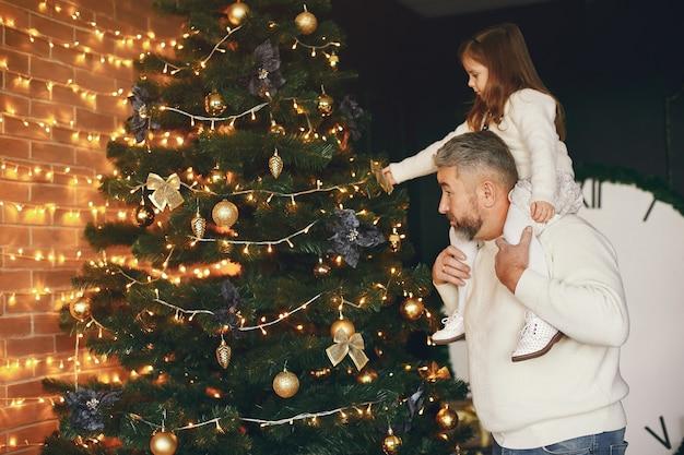 孫娘と一緒に座っている祖父。居心地の良い家でクリスマスを祝います。白いニットのセーターを着た男。