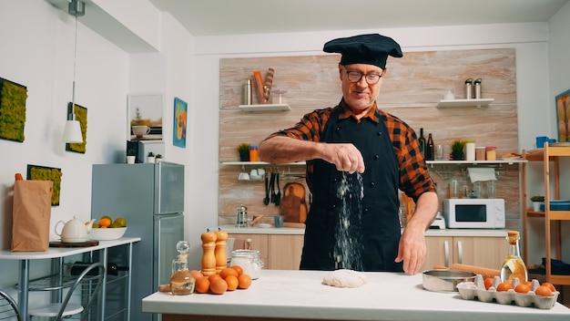 Nonno spolverata sul tavolo farina setacciata in cucina moderna. fornaio anziano anziano con bonete e setacciatura uniforme, setacciatura, diffusione di ingredienti rew sull'impasto, cottura della pizza e del pane fatti in casa.