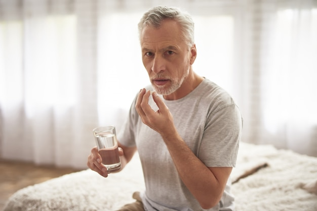 Grandfather taking pills in morning chronic pain.