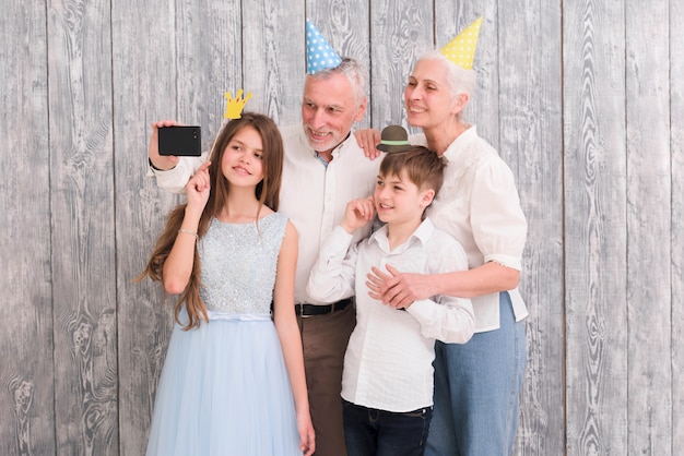 Grandfather taking selfie on mobile phone with his wife and grandchildren using props