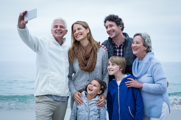 Grandfather taking selfie with cheerful family at sea shore
