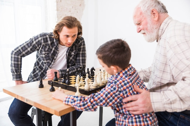 Grandfather teaching grandson playing chess