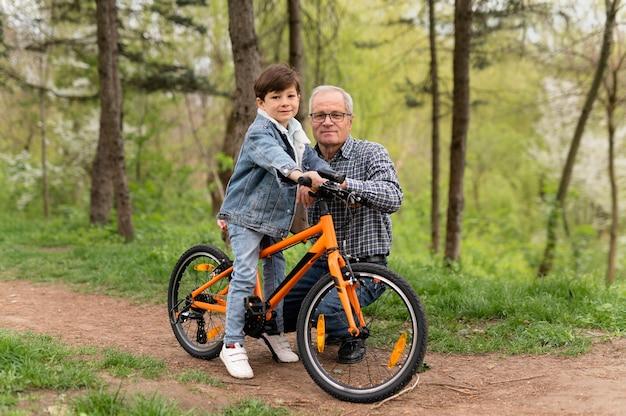 그의 손자에게 자전거를 타는 방법을 가르치는 할아버지
