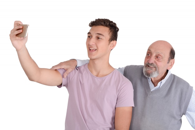 Grandfather and their teen grandson taking a selfie.