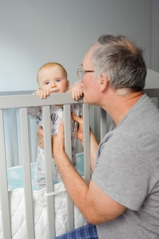 Grandfather training cute baby to stand. toddler standing in crib and looking at camera. vertical shot. child care or childhood concept