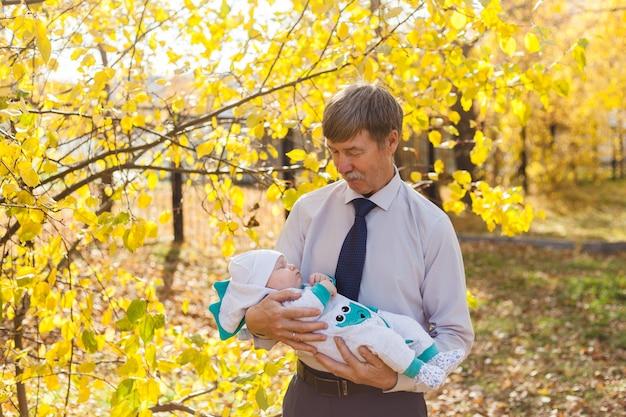 아기가있는 할아버지, 작은 소년이 공원이나 숲에서 가을을 산책합니다. 노란 잎, 자연의 아름다움. 자녀와 부모 간의 의사 소통.