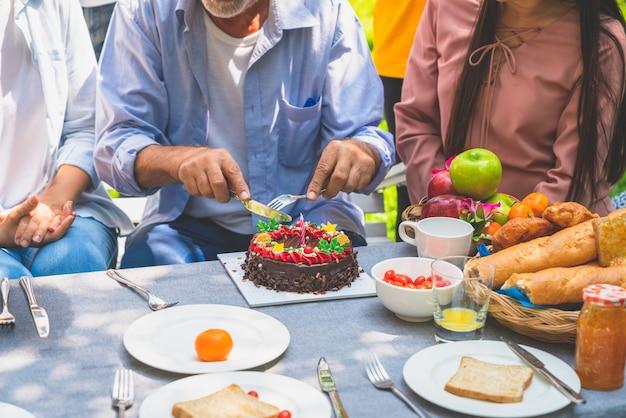 Дедушка с праздничным тортом на семейной вечеринке в саду дома