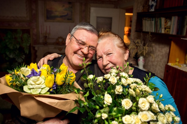 Grandfather with bouquets of flowers congratulates grandmother. elderly couple in love. pensioners kissing. family retired.