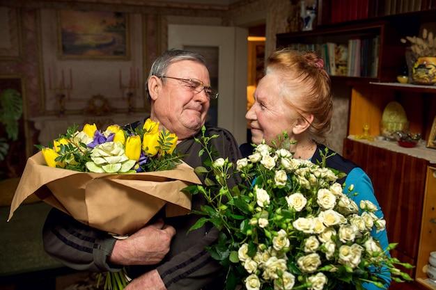 Дедушка с букетами цветов поздравляет бабушку. пожилая пара в любви. пенсионеры целуются. семья на пенсии.